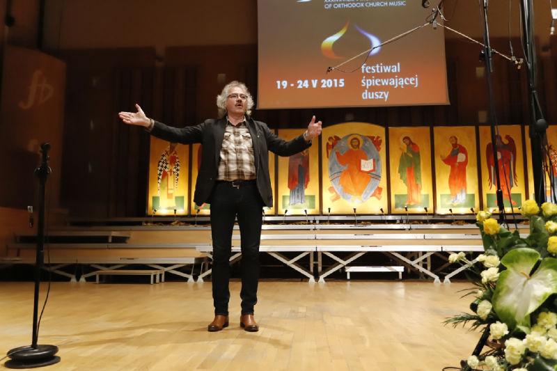 Janusz Siadlak dyryguje chórzystami zebranymi w sali koncertowej