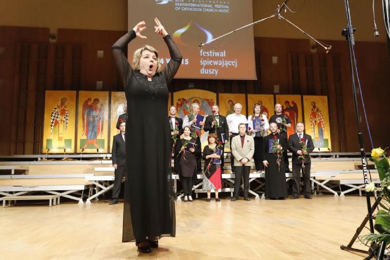 """Dyrygentka Julija Tkacz dyryguje publicznością – chórzystami wykonującymi """"Mnogaja leta"""""""